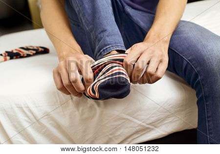 closeup of a young caucasian man wearing sitting on the edge of the bed putting on or taking off a pair of colorful striped socks