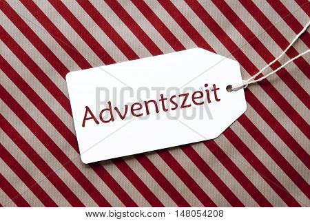 One Label On A Red And Brown Striped Wrapping Paper. Textured Background. Tag With Ribbon. German Text Adventszeit Means Advent Season