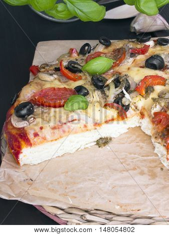 pizza with tomatoes mushrooms olives and peppers served on a wooden table