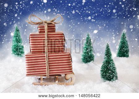 Sleigh With Christmas Gifts Or Presents. Snowy Scenery With Snow And Trees. Blue Background With Snowflakes
