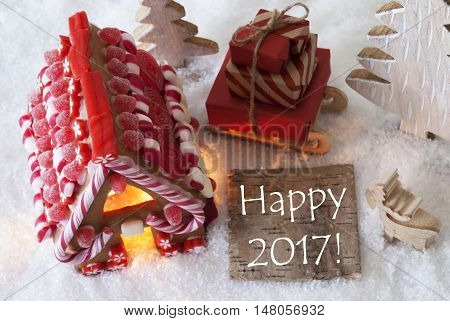 Label With English Text Happy 2017 For Happy New Year. Gingerbread House On Snow With Christmas Decoration Like Trees And Moose. Sleigh With Christmas Gifts Or Presents.