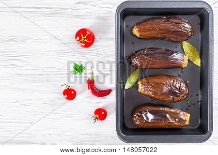 oven baked eggplants in baking dish with bay leaves and spices on white table view from above