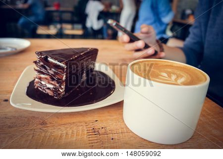 Coffee cup and chocolate cake on wood table background woman use mobile phone in coffee shop.