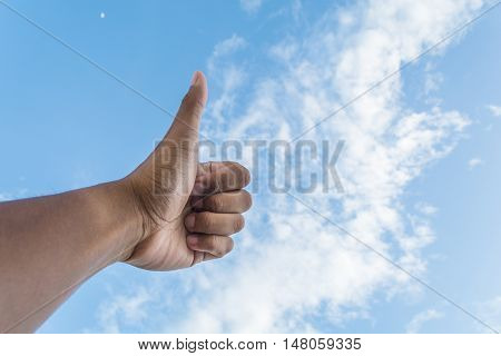 Asian man's thumb with bright blue sky and white cloud as background shows concept of good agreement and okay.