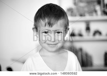 Portrait of a boy in his room. Little boy smiling and looking at the camera. Black and white image.