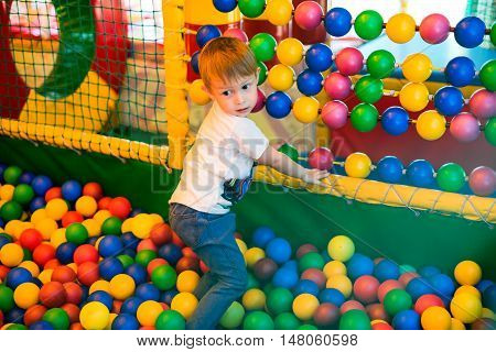 Boy playing on the playground in the children's maze with balls. Multi-colored balls soft walls and floor for children.