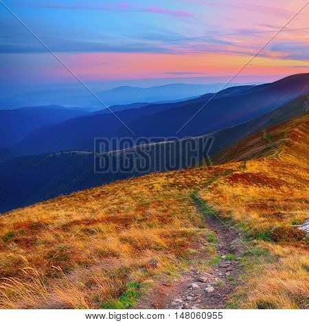 winding road through meadows of mountain range at sunset. Beautiful landscape in the mountain
