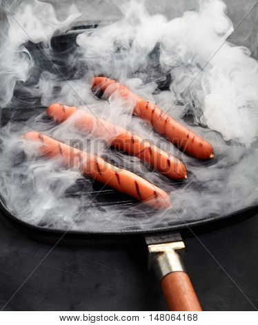Close-up view of three hot Vienna sausages on a Smoking grill pan on a gray background with a kitchen towel nearby. Ingredients for making homemade hot dogs. Perfect lunch, easy dish. Fast food snack