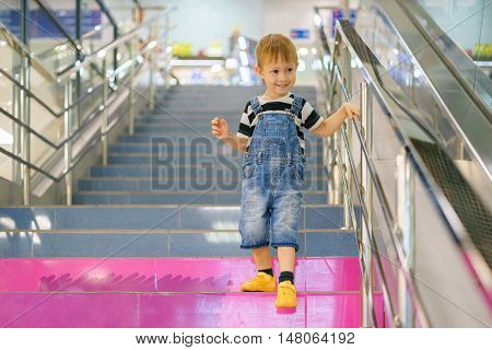 The boy comes down the stairs in a shopping mall. The staircase indoors