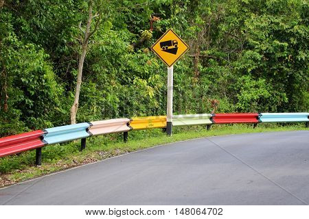 colorful guard rail sections near steep incline warning road sign on Songkhla Zoo access road, Songkhla, Thailand