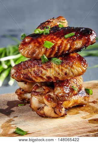 Close up view of delicious honey and mustard glazed roasted chicken wings topped with sliced green onions on a cutting wooden board. Delicious sticky treat. Blurred fresh green onion behind