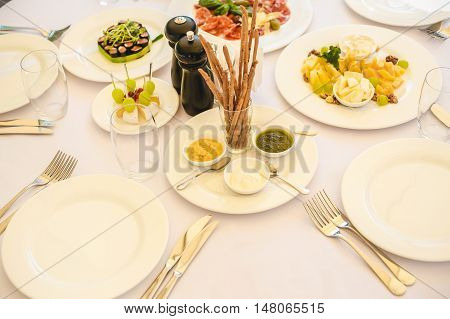 Beautifully decorated catering banquet table with different food snacks and appetizers with sandwich, caviar, fresh fruits on corporate party event or wedding celebration