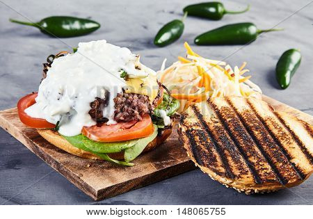 Gourmet homemade burger with beef, fried spicy jalapenos, fresh spinach, sliced tomatoes, cheese, grilled bun and sauce of yogurt and blue cheese. With coleslaw on wooden board. Jalapenos behind