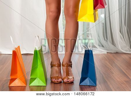 Beautiful female slender legs Woman holding a shopping bags