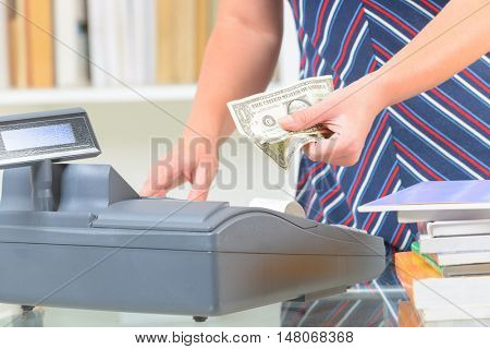 Seller using cash register at bookstore and holding money