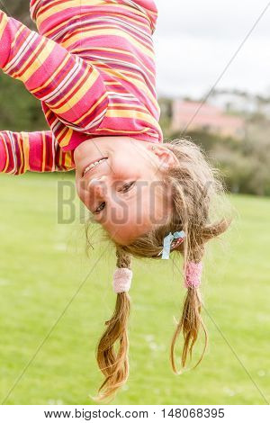outdoor portrait of smiling happy child girl playing upside down on natural background