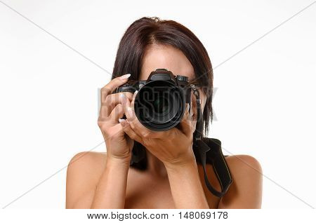 Young female photographer taking a photograph aiming the lens at the viewer head and shoulders isolated on white