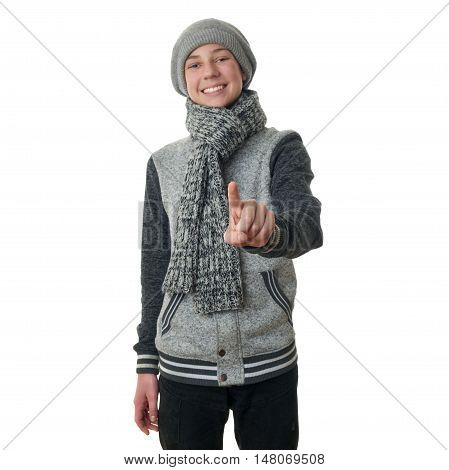 Cute teenager boy in gray sweater, hat and scarf pushing something in front himself over white isolated background, half body