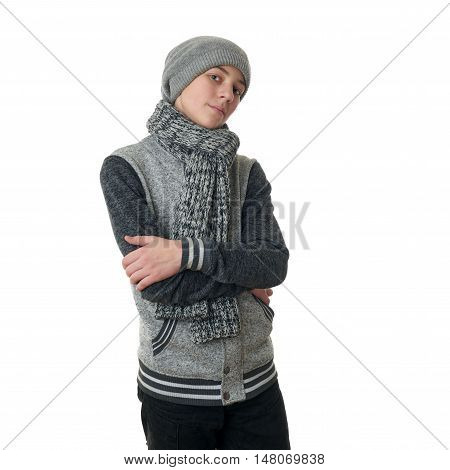 Cute teenager boy in gray sweater, hat and scarf with crossed arms over white isolated background, half body