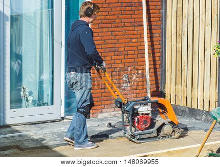 Contractor in headphones using a vibratory plate compactor to make the sand flat before paving
