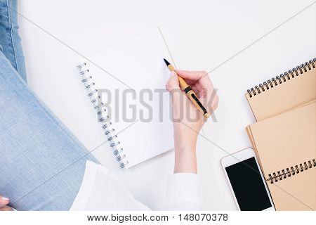 Top view of woman's hand writing in empty spiral notepad on white surface next to blank smartphone and other copybooks. Mock up