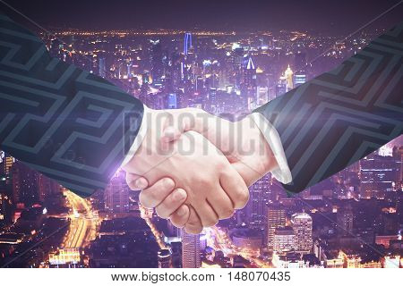 Businesspeople shaking hands on maze and illuminated night city background. Partnership and business challenge concept. Double exposure