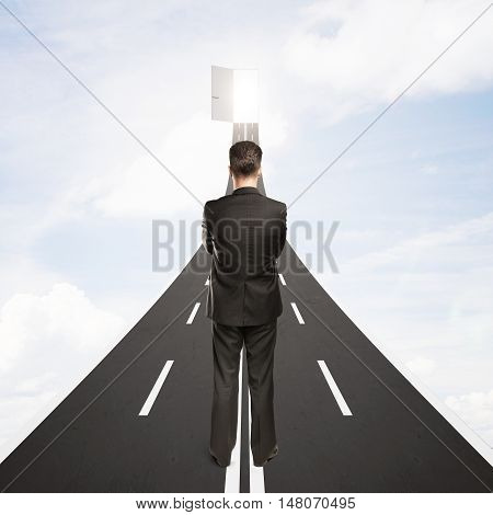Young businessman standing on road leading to abstract open door with possibilites on sky background. Success concept