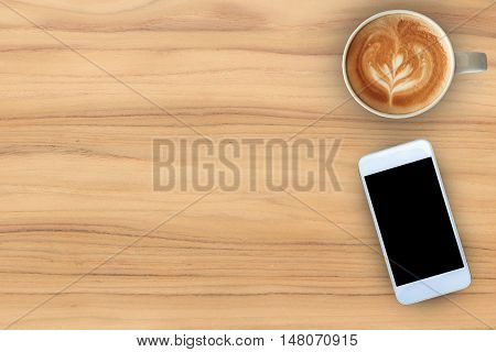 Coffee cup and mobile phone on teak wood texture background.
