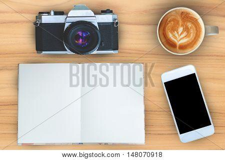 Coffeenotebookmobilephone and camera on teak wood texture background.