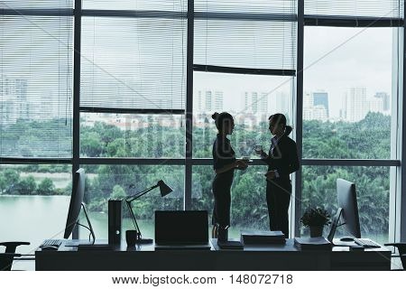 Businesswomen drinking coffee and talking in office on rainy day