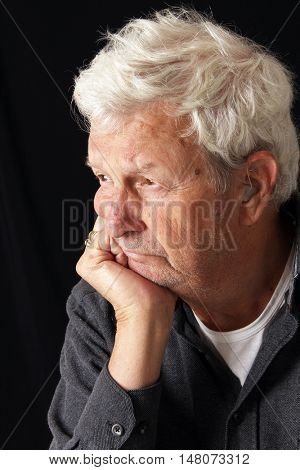 Senior gentleman with serious expression. Visible hearing aid.