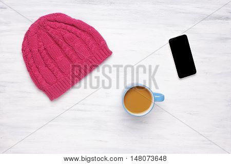 Top view of a cup of coffee and a knitted woman's hat on a white wooden table with a smartphone. Cozy atmosphere concept. Winter and autumn season.