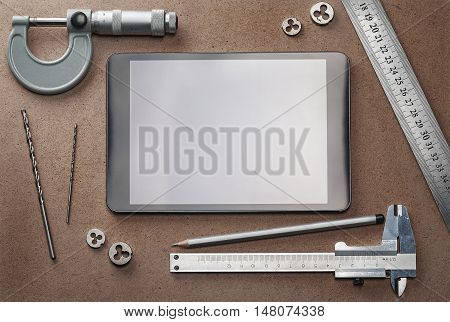 desktop with drills tablet calliper pencil and other