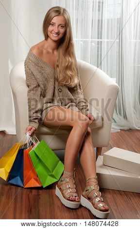 Beautiful female slender legs Woman holding a shopping bags sitting on a sofa