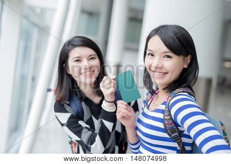 two beauty woman take passport go to travel and smile to you in hong kong airport asian