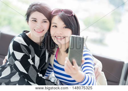 two beauty woman take smart phone and selfie in hong kong airport asian