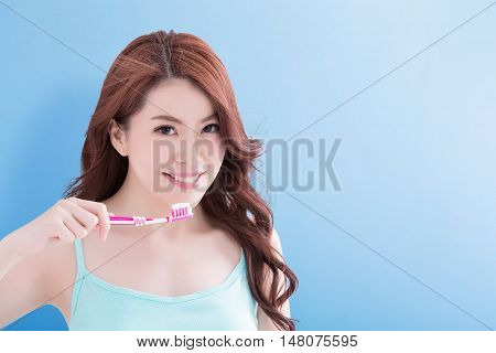 beauty woman take toothbrush and smile to you with blue background asian