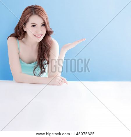 beauty skin care woman lying on the white table and show something to you with blue background asian