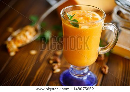 pumpkin smoothie with nuts and honey on a wooden table