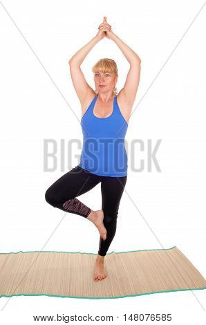 A lovely blond woman is yoga outfit standing on a mat on one leg a poses for yoga exercises isolated for white background.