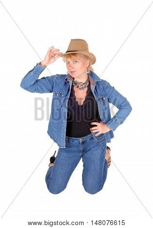A pretty woman in jeans and jeans jacket kneeling on the floor wearing a cowboy hat isolated for white background.