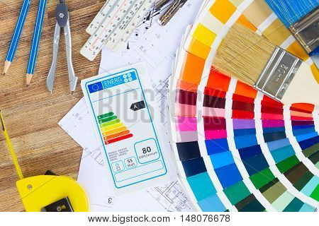 Interior designer's working table with energy rating chart, architectural plan of the apartment, color palette and brushes