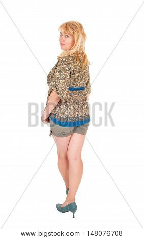 A middle age blond woman standing in shorts from the back looking over her shoulder isolated for white background.