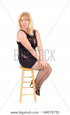 A beautiful woman in her forties sitting in a black evening dress and black stockings on a chair isolated for white background.