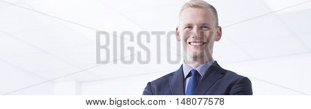 Young man in a suit he is standing and looking straight with a smile
