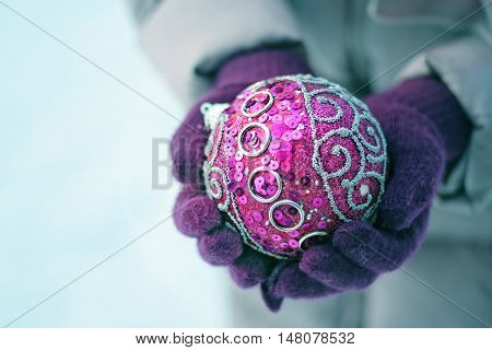 New Year's ball lies in mittens. New Year's lilac tone still life with soft Focus