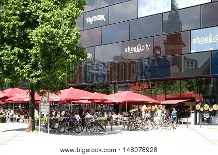 BERLIN, GERMANY - MAY 10: Guests and visitors sit in good weather in the cafe La Luna at Alexander square and eat ice and drink refreshment on May 10 2016 in Berlin.