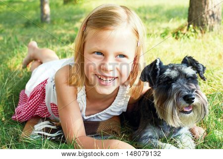 Happy cute little girl hugging her little dog