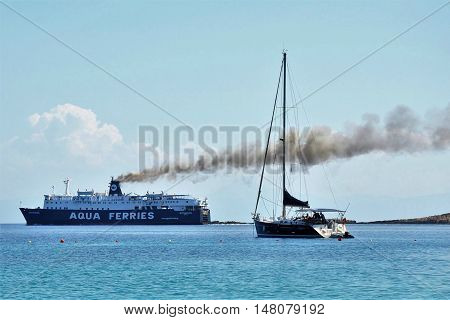 Alonissos, Greece - June 28, 2016: Cruise Aqua ferry ship on sea with big black smoke streak line from its chimneys, in contrast to a small fishing boat.