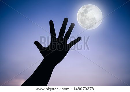 Silhouette Of A Hand With Full Moon On Fantastic Sky Background.